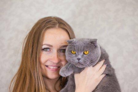 Photo pour Portrait d'une belle fille avec un chat. Une femme tient un chat dans ses bras. Les animaux de compagnie et leurs propriétaires. - image libre de droit