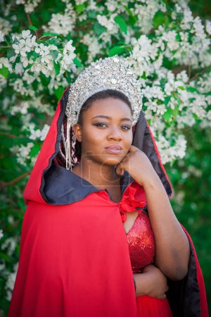 Photo for Queen in the crown and royal mantle. Lovely girl on the background of a blooming garden. African American in red - Royalty Free Image