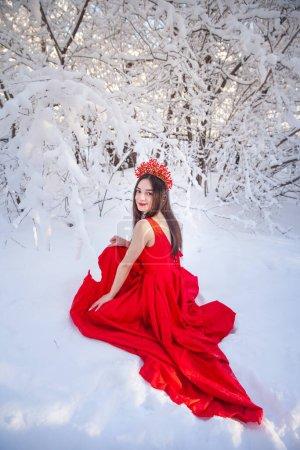 Königin in roter Krone inmitten des Winterwaldes. Schöne Mädchen in einem