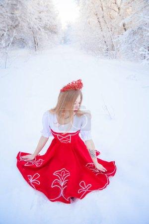 Königin in roter Krone inmitten des Winterwaldes. Schöne Mädchen in einem roten russischen Folk-Outfit. Attraktive Blondine