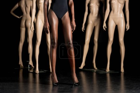 Photo for Cropped shot of african american woman in high heeled shoes standing between mannequins on black - Royalty Free Image