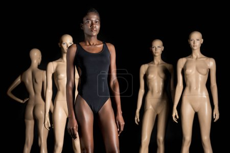 beautiful african american woman in bodysuit standing in front of dummies and looking at camera on black