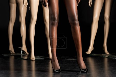 low section of african american woman in high heeled shoes standing between mannequins on black