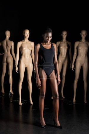 Photo pour Vue de la pleine longueur de belle jeune femme afro-américaine en maillot de bain debout devant les mannequins et regardant vers le bas sur fond noir - image libre de droit