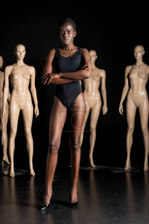 beautiful young woman in swimsuit looking at camera while standing with crossed arms in front of mannequins on black