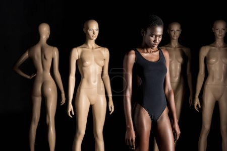 young african american woman in swimsuit standing in front of mannequins and looking down on black