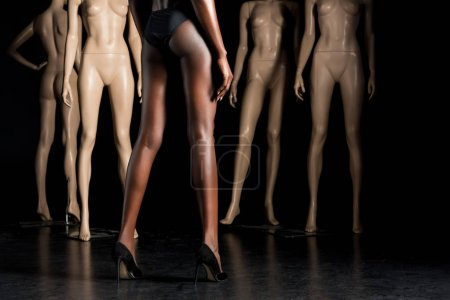 cropped shot of stylish african american woman in swimsuit standing in front of mannequins on black