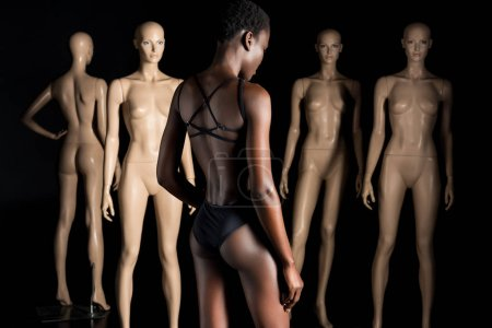 back view of stylish african american woman in swimsuit standing in front of mannequins on black