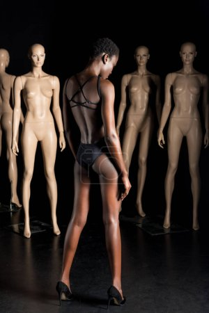 Photo for Back view of stylish african american woman in bodysuit standing in front of mannequins on black - Royalty Free Image