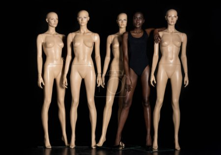 full length view of beautiful young african american woman in swimsuit standing between mannequins and looking at camera on black