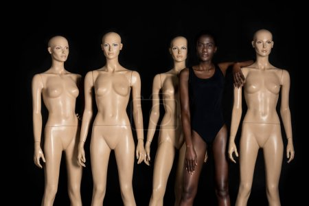 beautiful young african american woman in swimsuit standing between mannequins and looking at camera on black