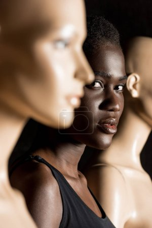selective focus of beautiful african american woman looking at camera while standing between dummies on black