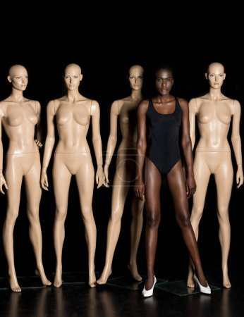attractive african american girl in leotard standing between dummies and looking at camera on black