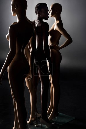 full length view of african american girl in swimsuit posing between mannequins on black