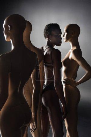 young african american model in bodysuit standing between dummies on black