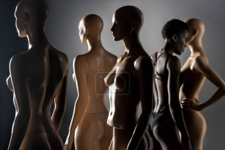 young african american woman in bodysuit standing between dummies on black