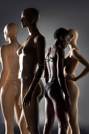 Photo for African american woman in bodysuit standing between mannequins on black - Royalty Free Image
