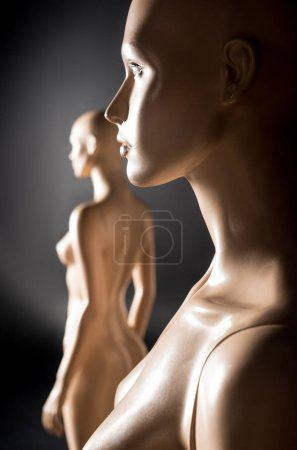 selective focus of two naked mannequins in studio on black