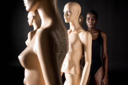 young african american woman in swimsuit looking at camera while standing behind mannequins on black