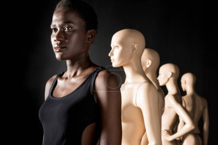 african american girl standing in row with mannequins and looking away on black