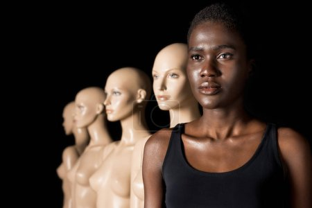 serious african american woman in swimsuit standing in row with mannequins on black