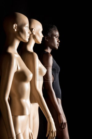 side view of young african american woman in swimsuit standing with dummies and looking away on black