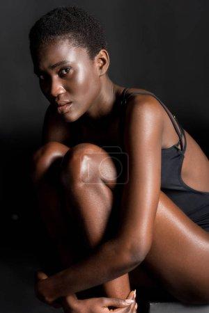 Photo pour Jolie fille afro-américaine en maillot de bain assis et regardant la caméra sur fond noir - image libre de droit