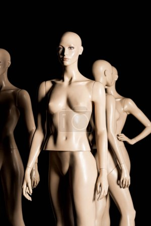 naked bald plastic mannequins on black