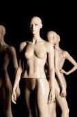 naked bald plastic mannequins on black