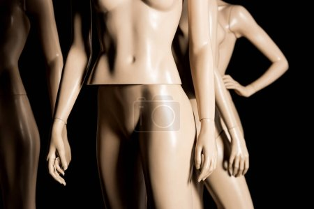 close-up view of naked plastic mannequins on black