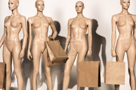 naked bald dummies with paper bags on white