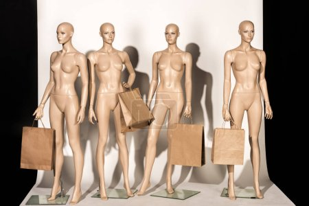 naked bald mannequins with shopping bags on white