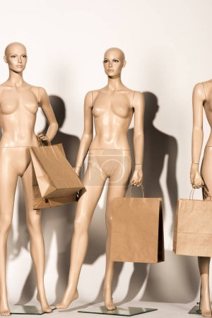 naked bald mannequins with paper bags on white