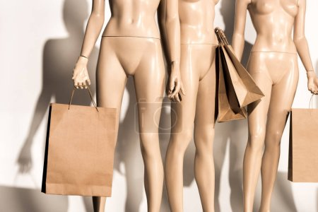 mid section of naked mannequins with shopping bags and shadows on white