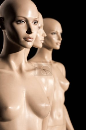 close-up view of naked bald mannequins on black, selective focus