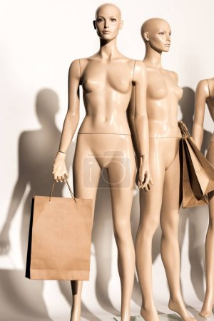 close-up  mannequins holding paper bags and shadows on white