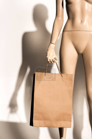 close-up view of naked mannequin holding shopping bag on white