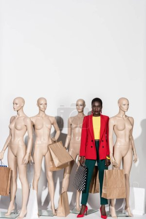 stylish african american girl looking at camera while standing between mannequins with shopping bags