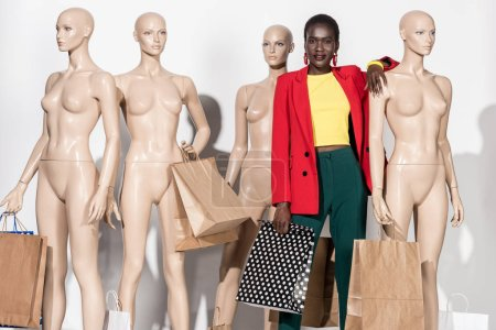stylish african american girl smiling at camera while standing between mannequins with shopping bags