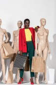 full length view of beautiful smiling african american girl standing between dummies with shopping bags on white