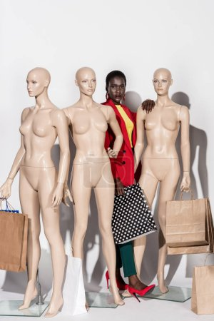 beautiful stylish african american girl looking at camera while standing between mannequins with shopping bags on white