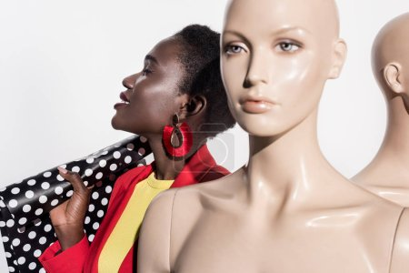 smiling young african american woman holding shopping bag and standing near mannequins on white