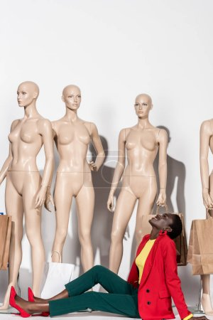 smiling stylish african american woman looking up while sitting in front of mannequins with shopping bags
