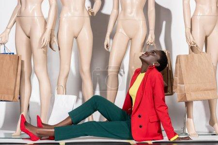 happy african american woman sitting in front of mannequins with shopping bags