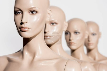 close-up view of naked bald mannequins in row on white, selective focus