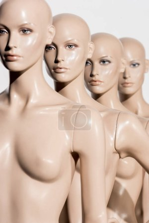 close-up view of naked bald dummies in a row on white