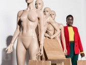 african american woman standing in row with mannequins holding paper bags on white