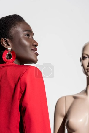low angle view of beautiful smiling african american woman standing near dummy and looking away on white