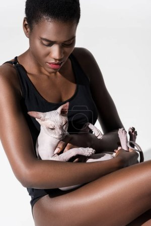 beautiful african american woman in bodysuit holding sphynx cat isolated on white