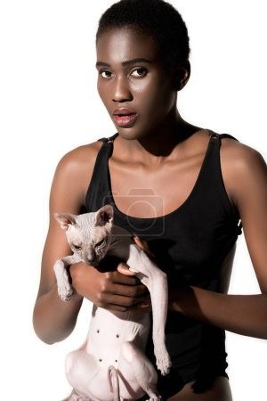 beautiful young african american woman in swimsuit holding cat and looking at camera isolated on white